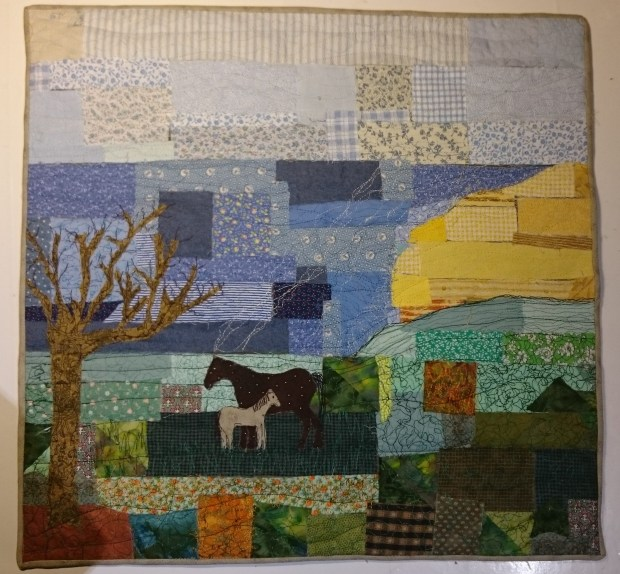 A fabric collage of sea, sky, the moors and two ponies under a tree