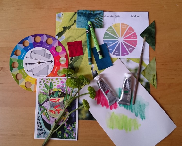 Items on a table to illustrate one of the classes offered by Amanda Jane Textiles, in this case the 'Inspired by Colour' class. There are two colour wheels, some fabric pieces, flowers, paints and paintbrush and wax crayons.