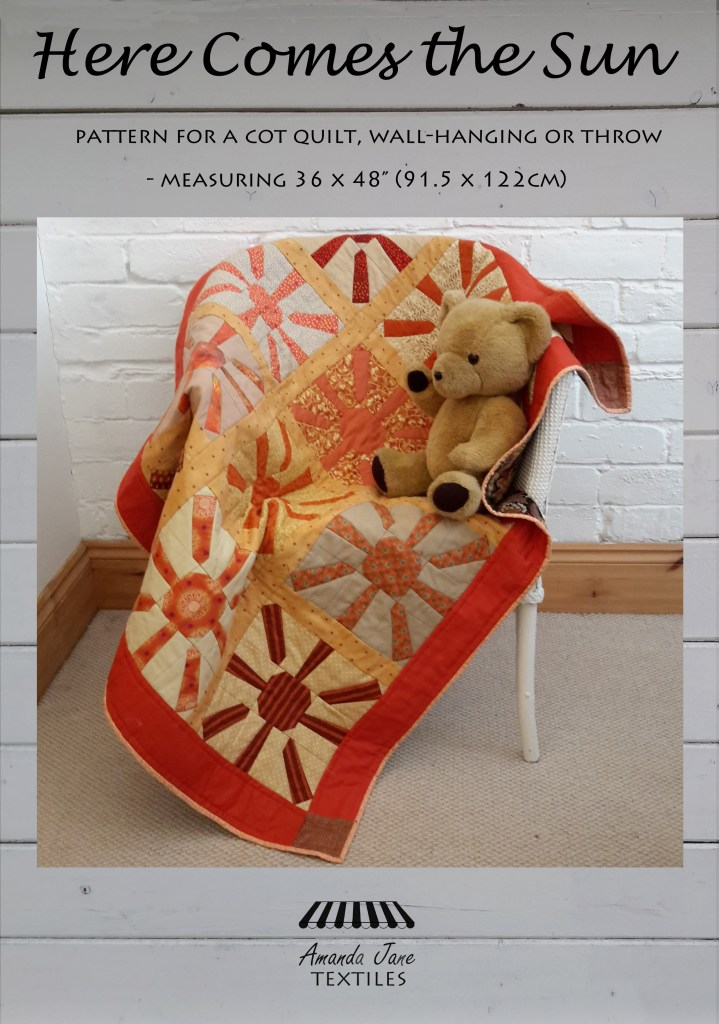 a cot quilt in oranges and yellows called 'Here Comes the Sun'