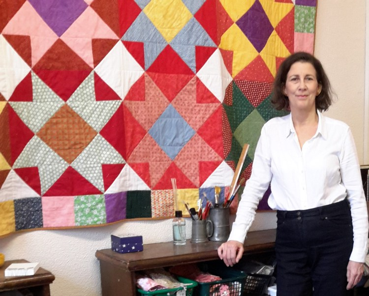 Amanda Jane Ogden standing in front of one of her quilts, the 'Mexico' quilt, featuring large-scale blocks in bold colours of red, green, yellow, purple and blue.