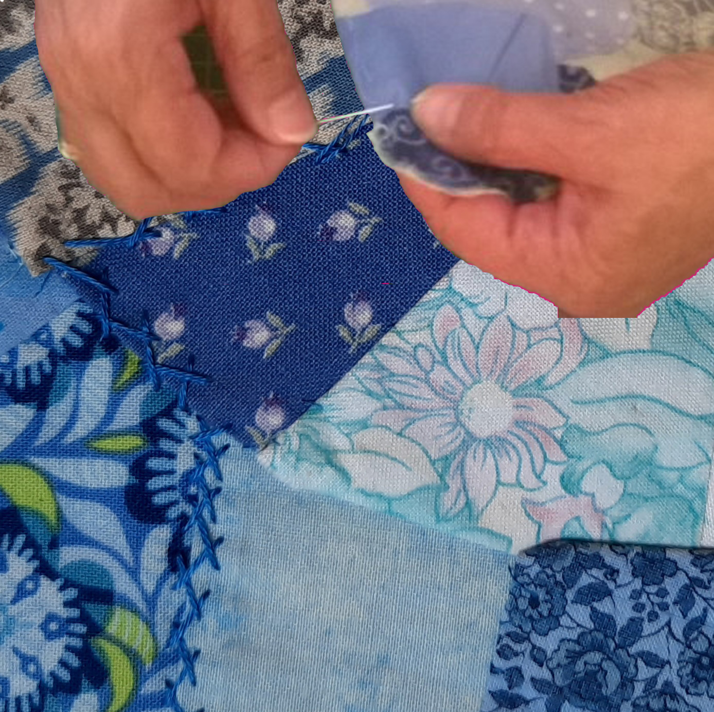 Hands holding a needle and embroidery thread, the person is working on a piece of crazy patchwork