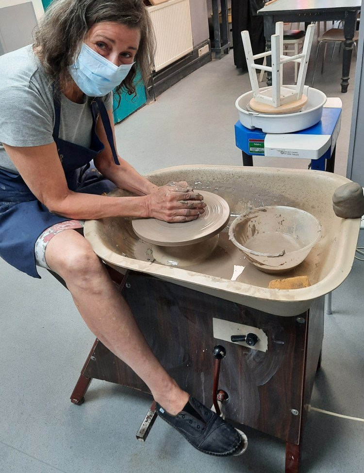 learning to centre a lump of clay on a potter's wheel