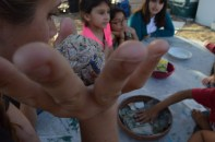 Jessica Moran holds up a seed bomb--strips of dried newspaper with flower seeds inside--as she explains to Garden Club members how to make them. Members were encouraged to spread the seed bombs in places they find to be ugly, with examples including empty
