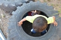 Two Garden Club members play in an old tire after they complete chores and before Moran teaches the lesson. Many Garden Club members are under the age of 10. (LaCasse/AP)