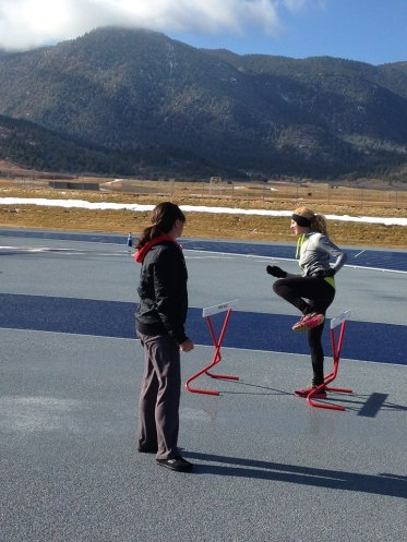 Coach Carrie Lane overseeing hurdle drills