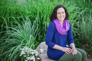 smiling woman sitting on rock