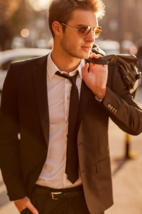 handsome young businessman holding a briefcase and walking in the street