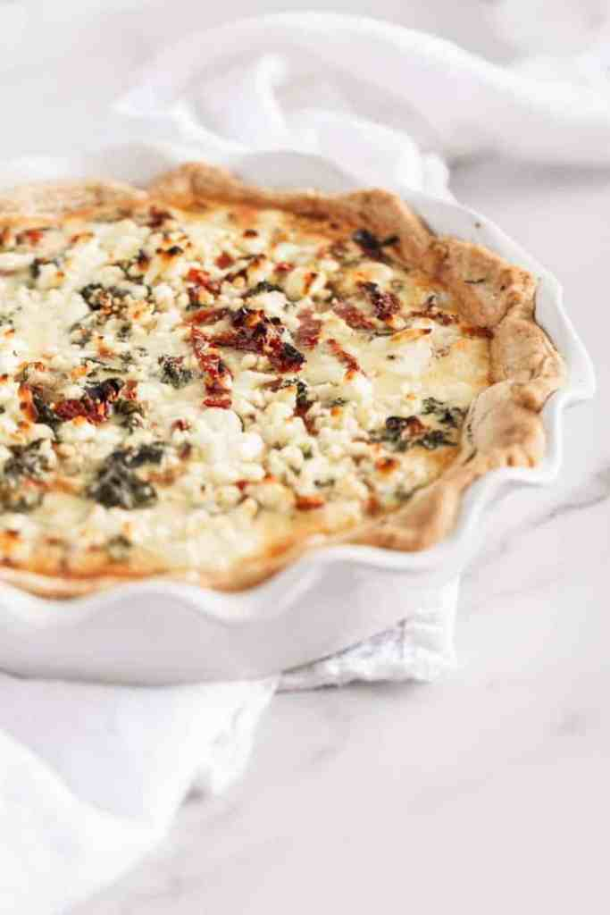 kale and sundried tomato quiche next to a plate