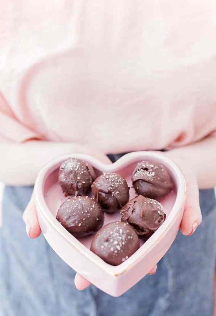 salted dark chocolate truffles in a heart shaped box being held by a woman