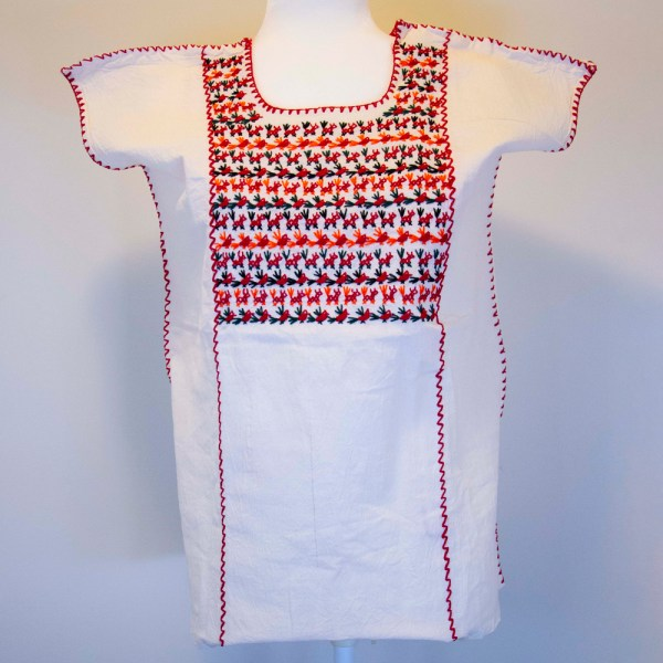 Traditional handmade Mexican embroidered white blouse made of cotton on a mannequin