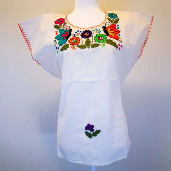 Front view of a Traditional handmade Mexican embroidered white blouse made of cotton on a mannequin