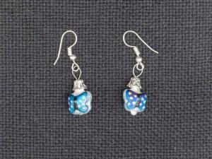 Handblown blue butterfly glass earrings on a gray fabric.