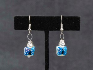 Handblown blue butterfly glass earrings shown hanging on a T earring display.