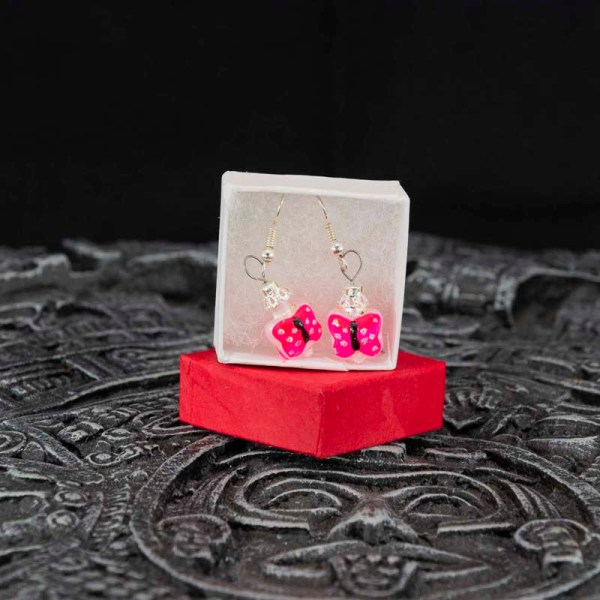 Handblown pink butterfly glass earrings displayed in an open blue box, Aztec calendar in the foreground, dark background