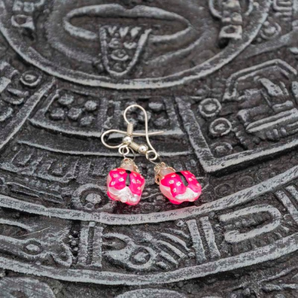 Handblown pink butterfly glass earrings displayed on top of an Aztec calendar