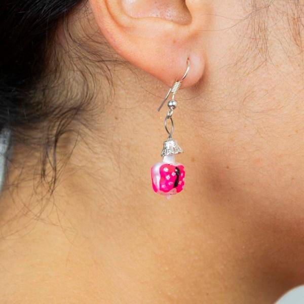Woman wearing Handblown pink butterfly glass earrings