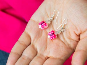 Handblown pink butterfly glass earrings shown on a hand.