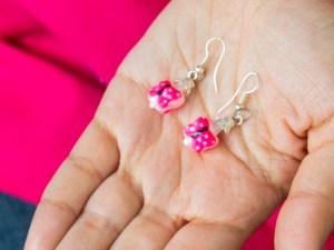 Handblown pink butterfly glass earrings shown on a hand.