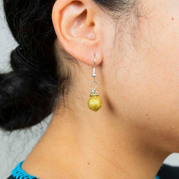 Woman wearing handblown glass golden earrings