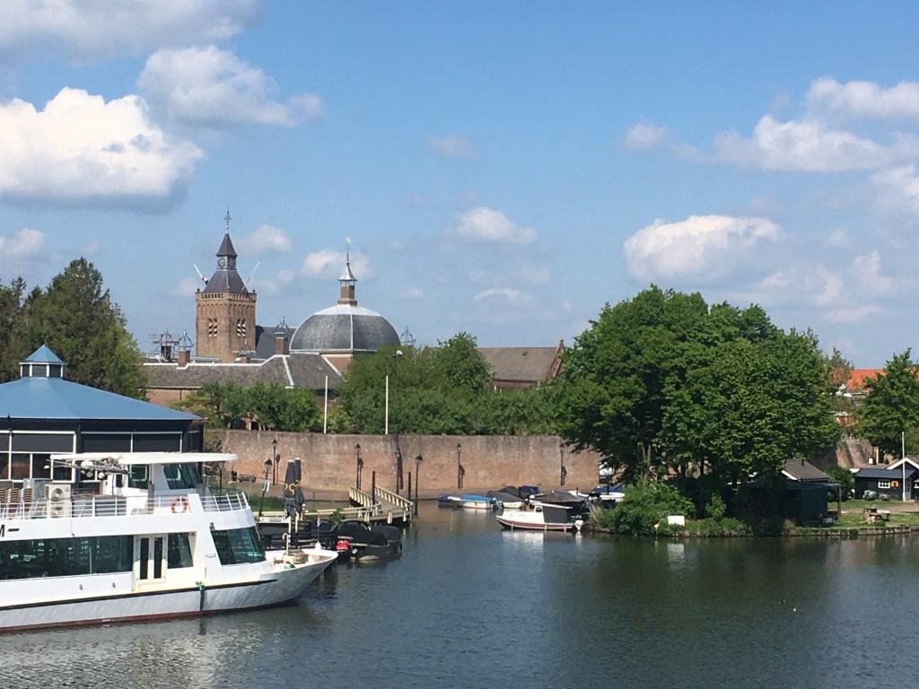 Zicht op Leerdam vanaf de Linge, met de kerktoren en het Hofje van Mevrouw Van Aerden.