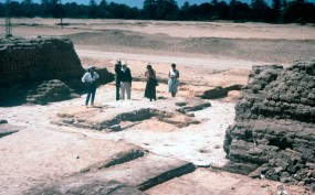 Architectural survey: In 1987 the project began a survey of previously excavated buildings, starting with the Small Aten Temple. Here the foundations of the doorway between the outermost brick pylons have been exposed. Originally floored with stones, with a low platform in the centre, what survives is a thick foundation layer of gypsum which preserves the clear imprint of the individual stones. Architect Michael Mallinson stands in the centre of the group.