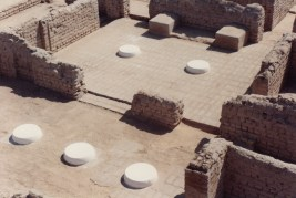 A repaired house: This house of an official (or nobleman, name unknown) lies not far south of the Small Aten Temple. It has house number Q44.1 and was excavated by the Egypt Exploration Society in 1923. Repairs began in the 1990s. A damaged brick floor has been made anew and new column bases installed. Further work is intended, including the insertion of a replica stone threshold in the main doorway to the central hall. Visitors to the site are able to see the whole house from a viewing platform built atop an adjacent spoil heap.