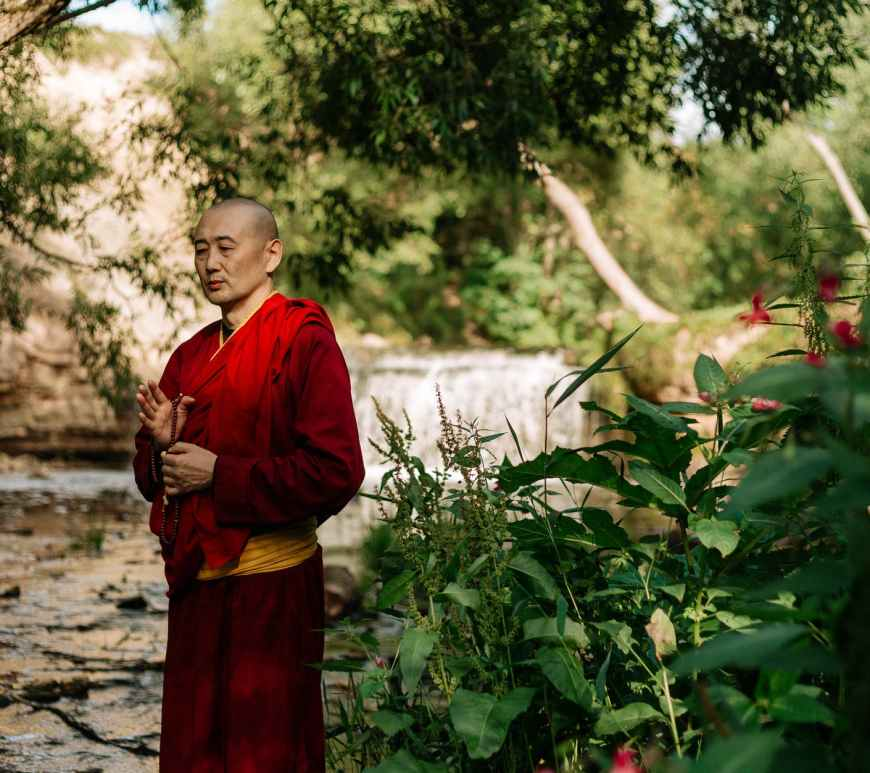 a monk standing while praying outdoors