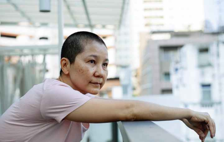 hopeful asian woman suffering from cancer in terrace of hospital- resilience is the ability to fight pain.