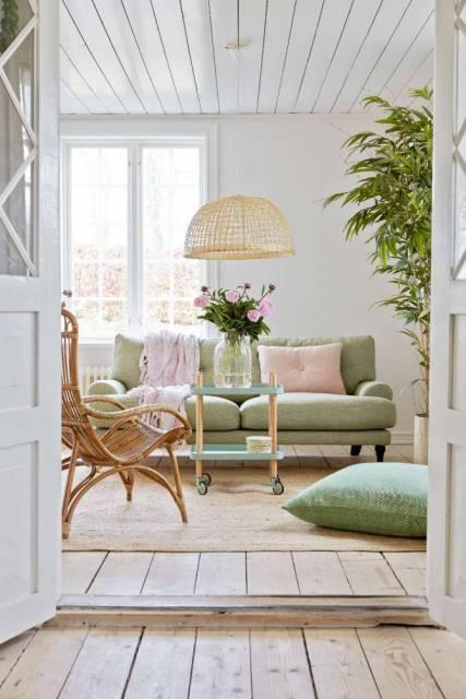 Soggiorno rustico dominato da colori verde pastello, rosa e bianco