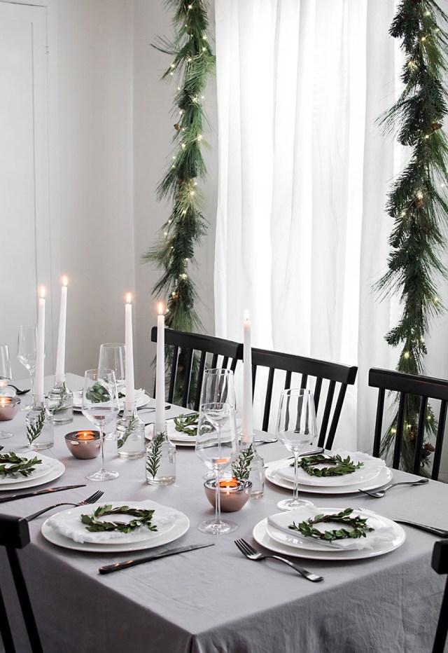 Una morbida tovaglia di lino e sobrie ghirlande per questa tavola di Natale in stile scandinavo
