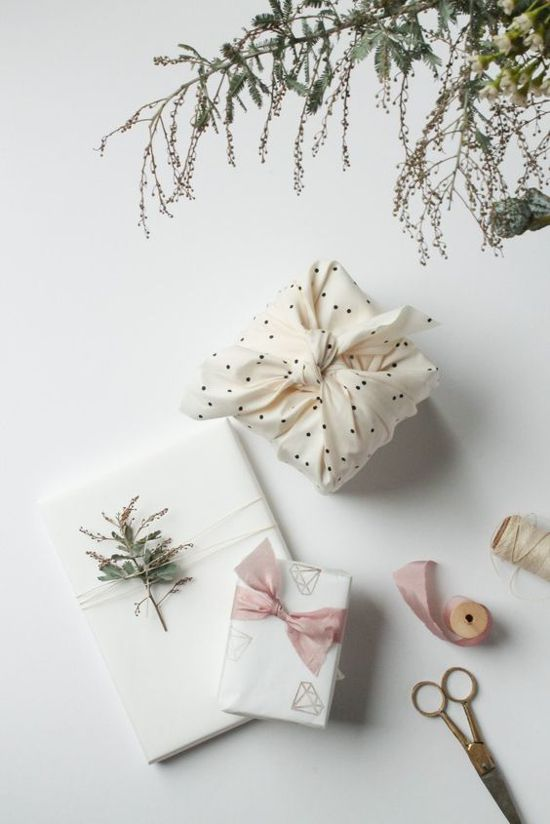 Confezioni regalo di Natale bianchi realizzati con carta e stoffa
