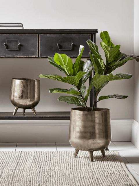 Un bella pianta artificiale in vaso metallico con piedi