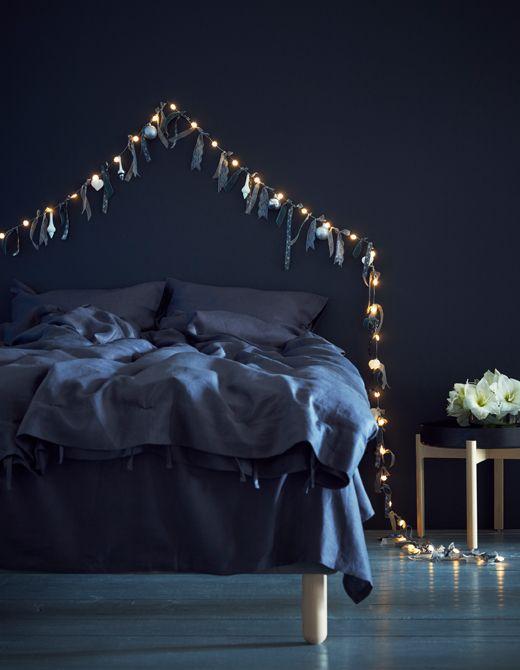 Camera da letto dai toni del blu con una semplice ghirlanda dorata a creare la perfetta atmosfera natalizia