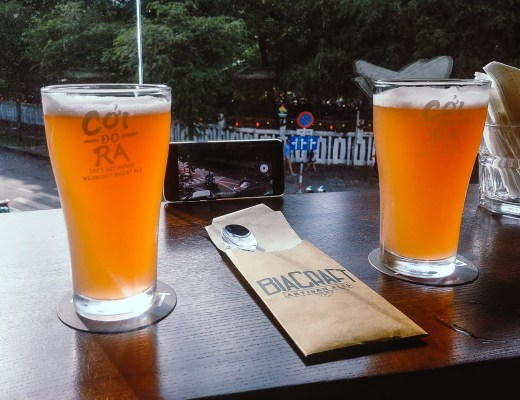 Two beautiful pints of golden beer on a window seal with a view of a busy Vietnamese street below. Photo taken at BiaCraft bar in District 1 ..