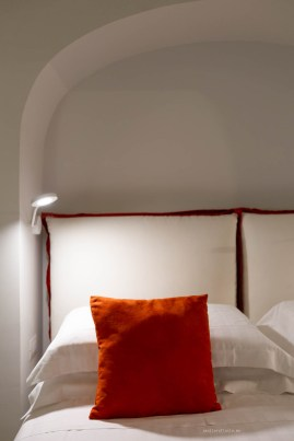 bedroom detail - white bed head, a reading lamp and a orange-red cushion.