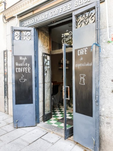 """The entrance to the Zero Point Coffee Shop with """"high quality coffee"""" written on a chalkboard."""