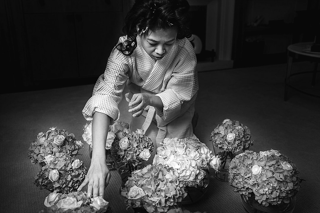 Corinthia Hotel Wedding Photographer Bride arranging flowers