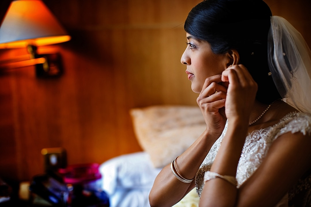 vill Court Wedding Photography Bride putting on her ear rings