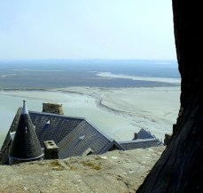 I paused as we climbed the winding streets to the top of Mont Saint-Michel and took this photo past the gnarled tree, over the rooftops and onto the horizon. The tiny people exploring the marshes come up clearly when the zoom is applied. https://amaviedecoeurentier.wordpress.com/2015/01/31/mont-saint-michel/