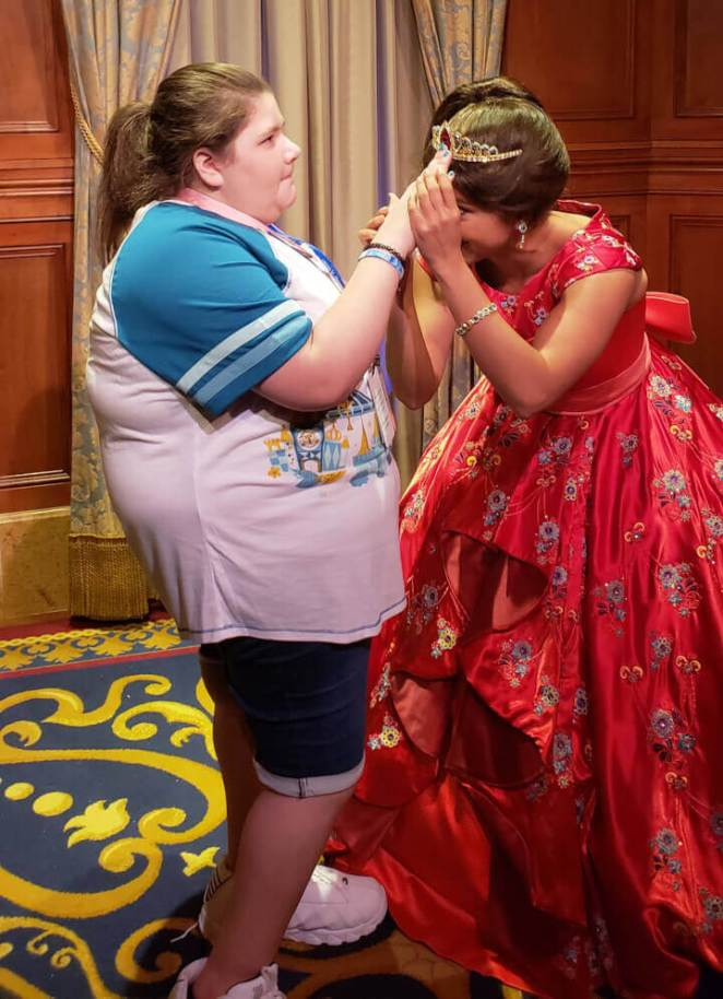 A Disney princess letting a blind fan touch and feel her crown and dress