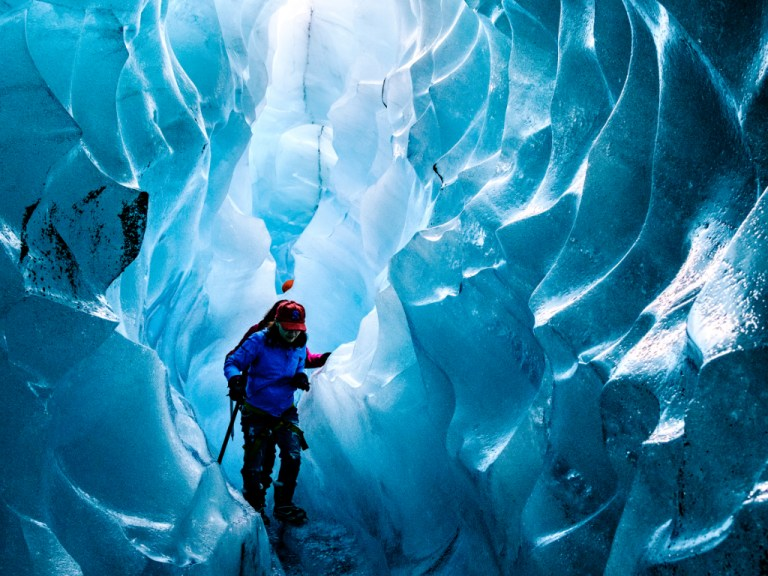 Hikers walking through a crevasse