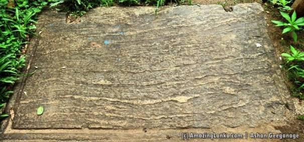 A large granite flower pedestal of the ancient past now lies on the floor at a door step to wipe the sand off the feet at Handapangala Weherayaya Sri Gangarama Rajamaha Viharaya