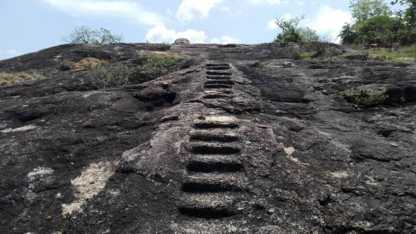 Steps cut in to the rock leading to the ruined stupas at the top at the Monaragala Veheradivulana Archaeological Site