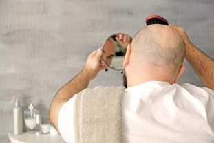Bald adult man with hair brush looking in mirror at home