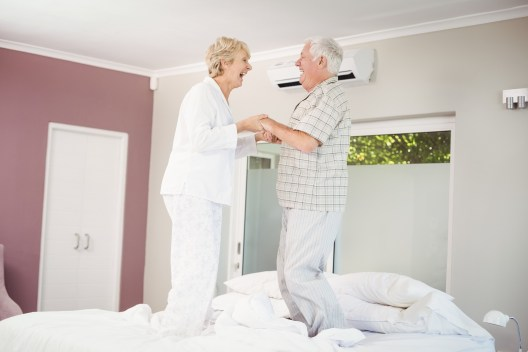 Cheerful senior couple jumping on bed in room