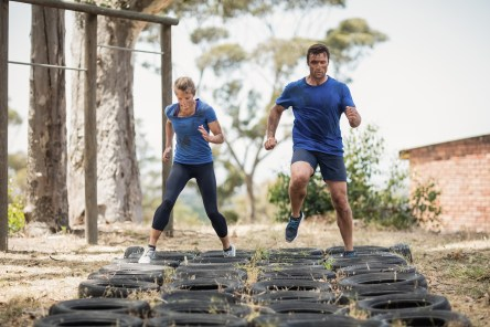 Man and woman running over the tyre during obstacle course in bo