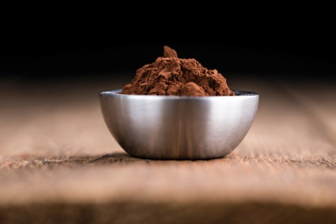 Cocoa powder (selective focus) as detailed close-up shot on wooden background