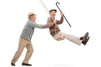 Two joyful senior gentlemen swinging on a swing and having fun i