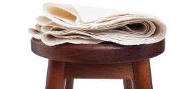 Natural And Organic Cotton Fabric Folded Sitting On Wooden Chair