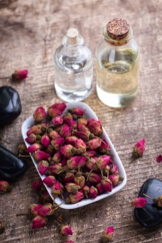 Dry roses flowers and bottles with essential aroma oil